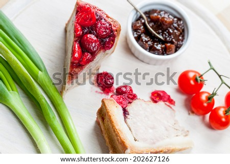 Pork and turkey pie with cranberries, chutney, tomatoes and spring onions on a wooden cutting board