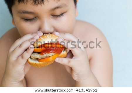 pork cheese Hamburger in obese fat boy hand on gray background - stock photo