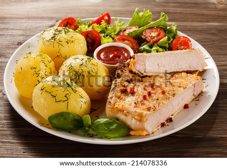 Pork chop, boiled potatoes and vegetables - stock photo