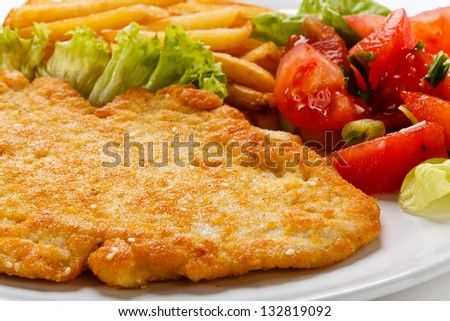 Pork chop, French fries and vegetables - stock photo