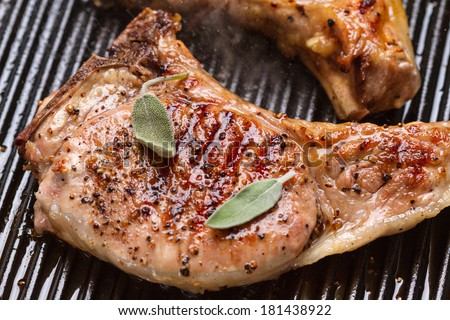 Pork chop with clary in a frying pan grill closeup - stock photo