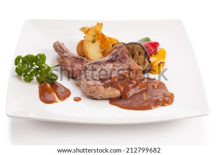 pork chop with mushroom sauce and roasted vegetable on plate isolated on white. - stock photo