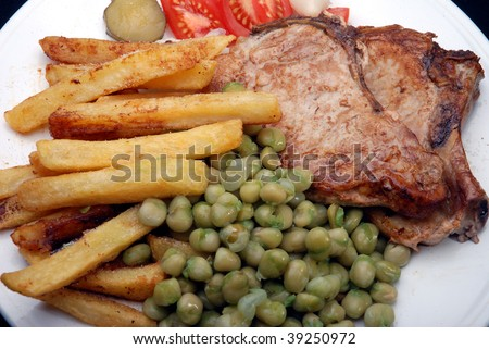 Pork chops chip and peas, typical English pub lunch.