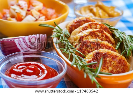 Pork chops, ketchup, onion, mustard and salad on blue napkin. - stock photo
