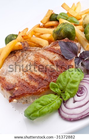 pork chops with french fries, brussels sprouts and red onions