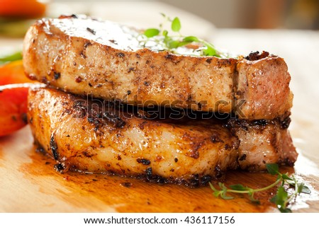 pork chops with vegetable and thyme on wooden board - stock photo
