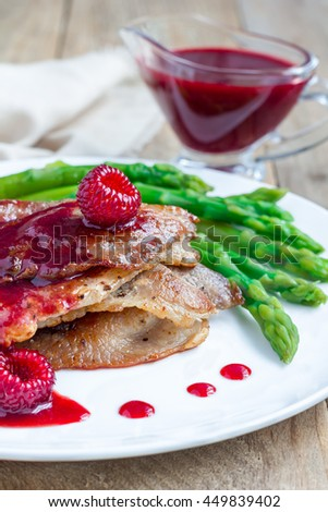 Pork cutlets with raspberry sauce and asparagus on white plate, vertical - stock photo