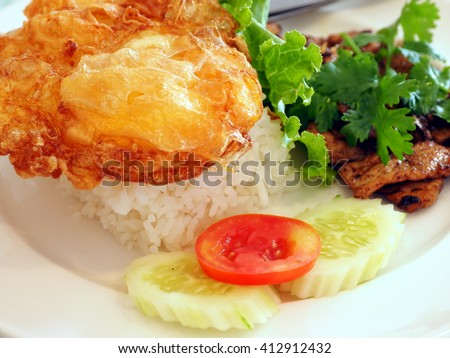 pork fried garlic with rice and fried egg; soft focus