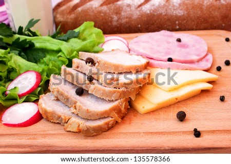 pork, ham, cheese and vegetables on a wooden board