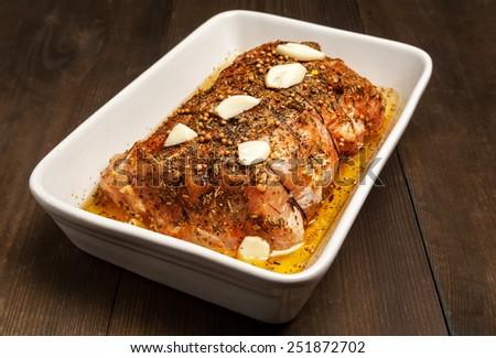 pork in roasting dish - preparation of meat - stock photo