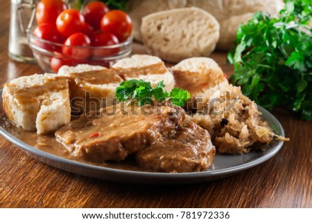 Pork loin in gravy with bread dumplings and sauerkraut. Czech cuisine