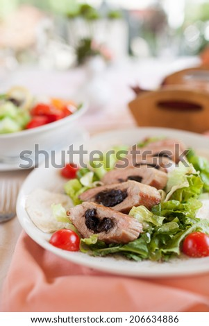 Pork loin with dried plums and salad - stock photo