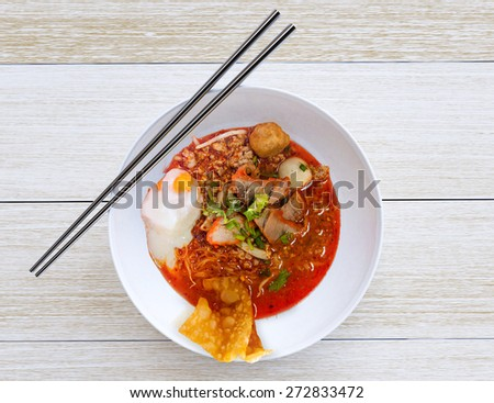 Pork noodle tom yum. spicy thai noodle  on wood floor - stock photo