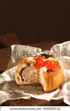 Pork pie on rustic wooden board with slice taken out - stock photo