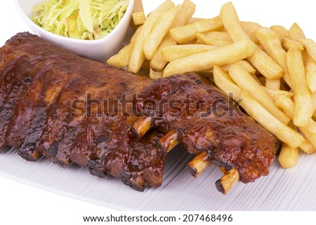 Pork ribs back with french fries and coleslaw salad on the side. Close up.