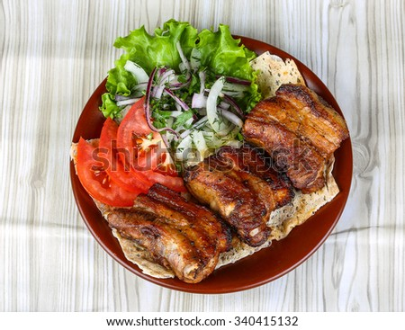 Pork ribs bbq with tomato, bread, salad leaves and onion - stock photo