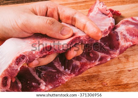 Pork Ribs, Raw. Organic Fresh Meat on Wooden Chopping Board with Chefs Hand. Preparation for Cooking or Grill. Background and Textures, Country Rustic Still Life Style.