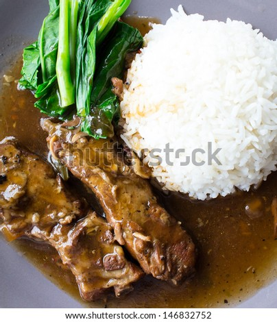 Pork ribs with sauce and cooked rice. - stock photo