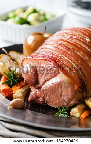 Pork roast served with baked apples and roasted vegetables, traditional family lunch dinner meal  - stock photo