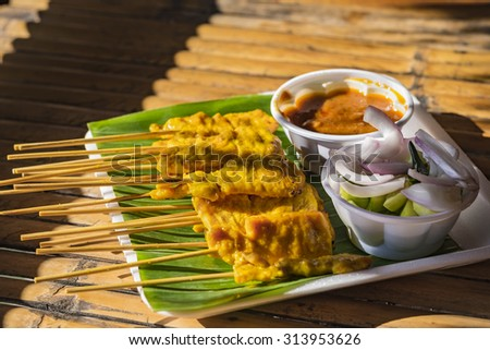 Pork satay served with peanut sauce and cucumber in vinegar - stock photo