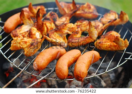 pork sausages  and chicken wings on smoking grill in the garden - stock photo