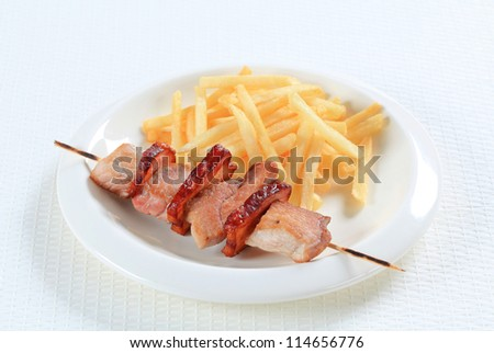 Pork skewer served with French fries