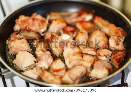 Pork slices on frying pan on gas station