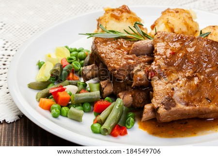 Pork spareribs served with mashed potatoes on a plate