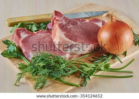pork stake, knife, onions and greens on a board, the meat cut on pieces before preparation - stock photo