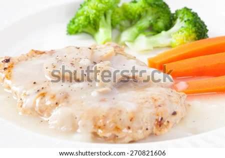 Pork steak with mushroom sauce sprinkle with pepper - stock photo