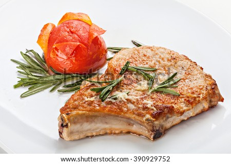 Pork steak with tomato on a plate decorated with a sprig of rosemary. Close-up. - stock photo