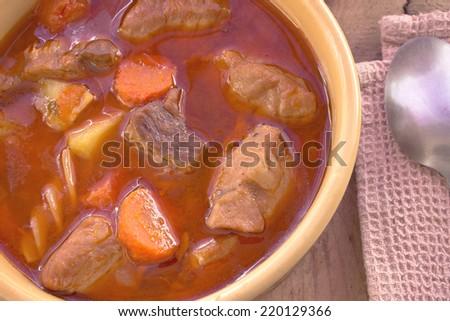 Pork stew in ceramic bowl on wooden background - stock photo