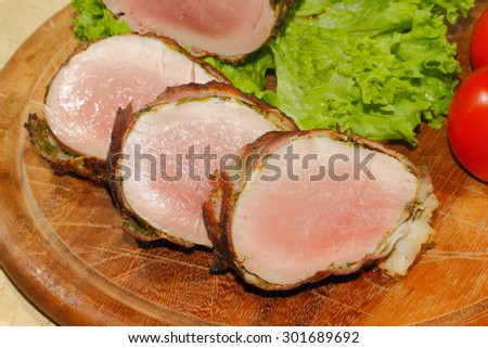 Pork tenderloin, pork medallions, pork, meat wrapped in bacon, grilled and garnished with lettuce and tomato on a wooden chopping board - stock photo
