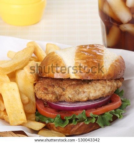 Pork tenderloin sandwich with lettuce, onion and tomato