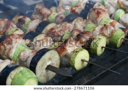 Pork with zucchini and eggplant roasted on skewers closeup - stock photo