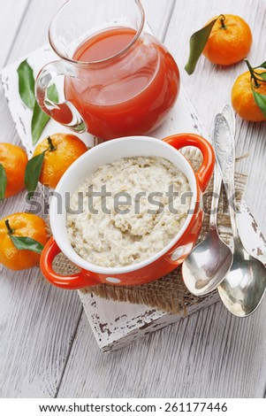 Porridge in an orange bowl, juice and mandarins on the table - stock photo