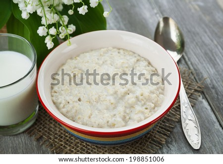 Porridge, milk and lily of the valley on the table - stock photo