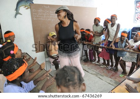 PORT-AU-PRINCE - AUGUST 25: A school teacher dancing in front of her  students in one of the schools in Cite Soleil,  in Port-Au-Prince, Haiti on August 25, 2010.  - stock photo