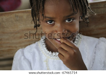 PORT-AU-PRINCE - AUGUST 22: A smiling unidentified kid during a food distribution camp in a broken church ,in Port-Au-Prince, Haiti on August 22, 2010. - stock photo