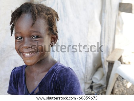 PORT-AU-PRINCE - AUGUST 28:  A young newsworthy girl sharing a laugh  outside her tent  in Port-Au-Prince, Haiti on August 28, 2010. - stock photo