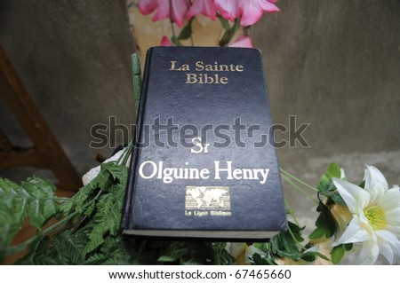 PORT-AU-PRINCE - AUGUST 22: An Haitian Bible lies on the rock of a broken church during a Sunday prayer in Port-Au-Prince, Haiti on August 22, 2010. - stock photo