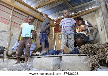 PORT-AU-PRINCE - AUGUST 28: An Haitian unidentified family in their temporary shack to escape from the scorching heat of their actual tent , in Port-Au-Prince, Haiti on August 28, 2010. - stock photo