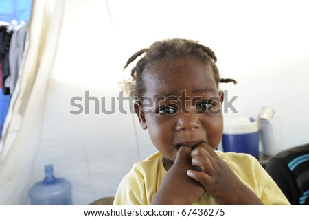 PORT-AU-PRINCE - AUGUST 28:   An unidentified  Haitian kid  biting her fingers out of starvation in , Port-Au-Prince, Haiti on August 28, 2010. - stock photo