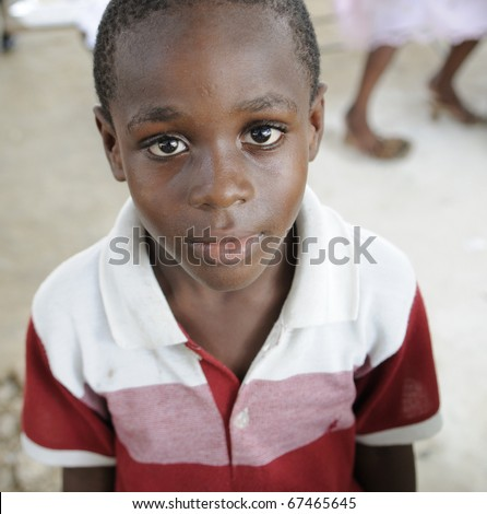 PORT-AU-PRINCE - AUGUST 22:  Innocent look of an unidentified Haitian child during a food distribution camp in Port-Au-Prince, Haiti on August 22, 2010. - stock photo