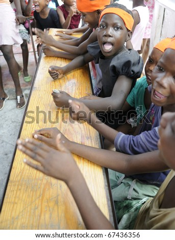 PORT-AU-PRINCE - AUGUST 25: unidentified Kids banging their desks while singing their prayer in on of a local school in Cite Soleil- in Port-Au-Prince, Haiti on August 25, 2010. - stock photo