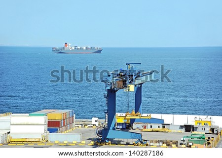 Port cargo crane, container and ship over blue sky background