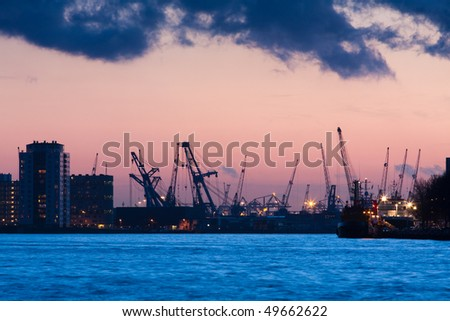 Port city at night. Cranes and river