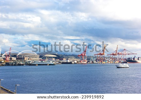 Port cranes and buildings under blue cloudy sky in Seattle downtown. Late afternoon sun touched Seattle port pier. - stock photo