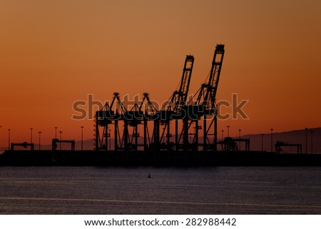 Port cranes in the sunset - stock photo