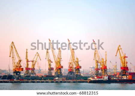 Port cranes loaded cargo on the ship - stock photo